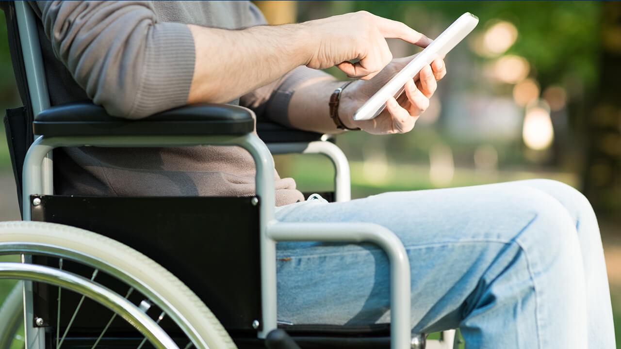 Rollstuhlfahrer mit Handy in der Hand auf Informationssuche fuer Camping mit Handicap