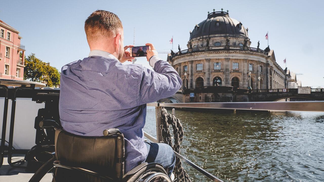 Rollstuhlfahrer fotografiert eine Sehenswuerdigkeit in Berlin mit dem Handy auf einer Reise mimt Rollstuhl