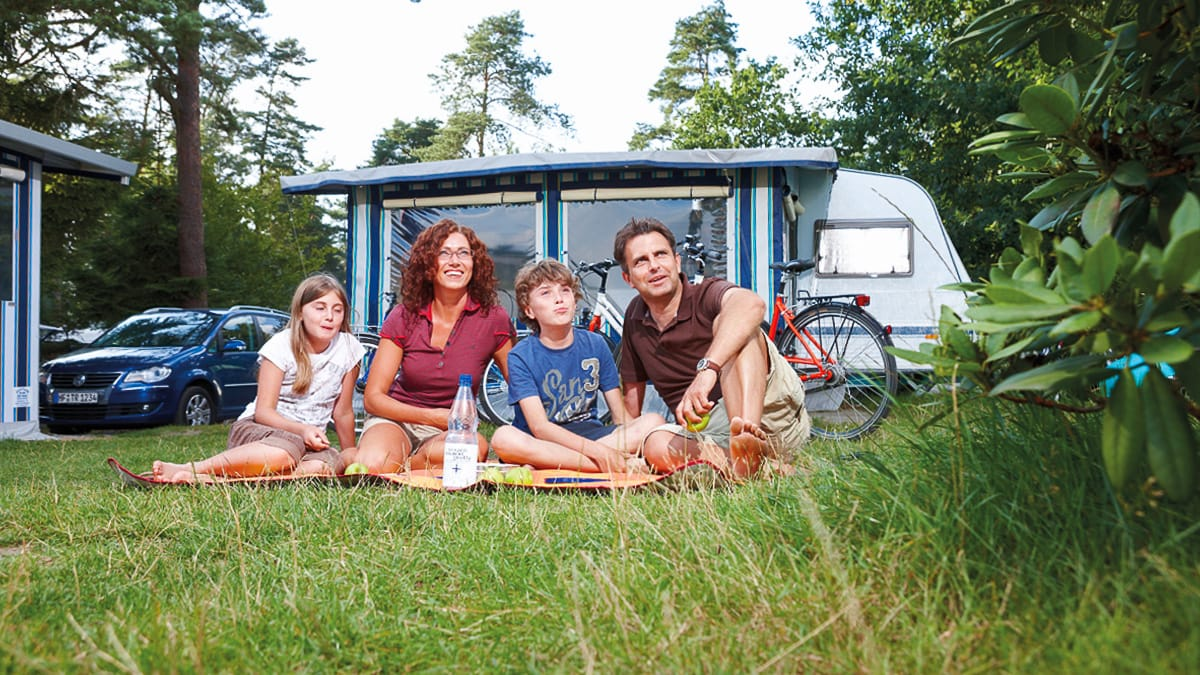 Eine Familie vor dem Camper auf dem Campingplatz