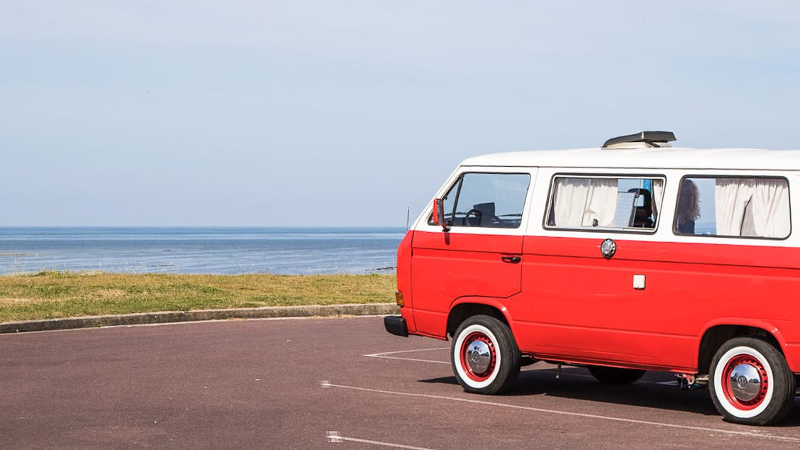 Ein roter Bulli beim Camping in Frankreich am Meer