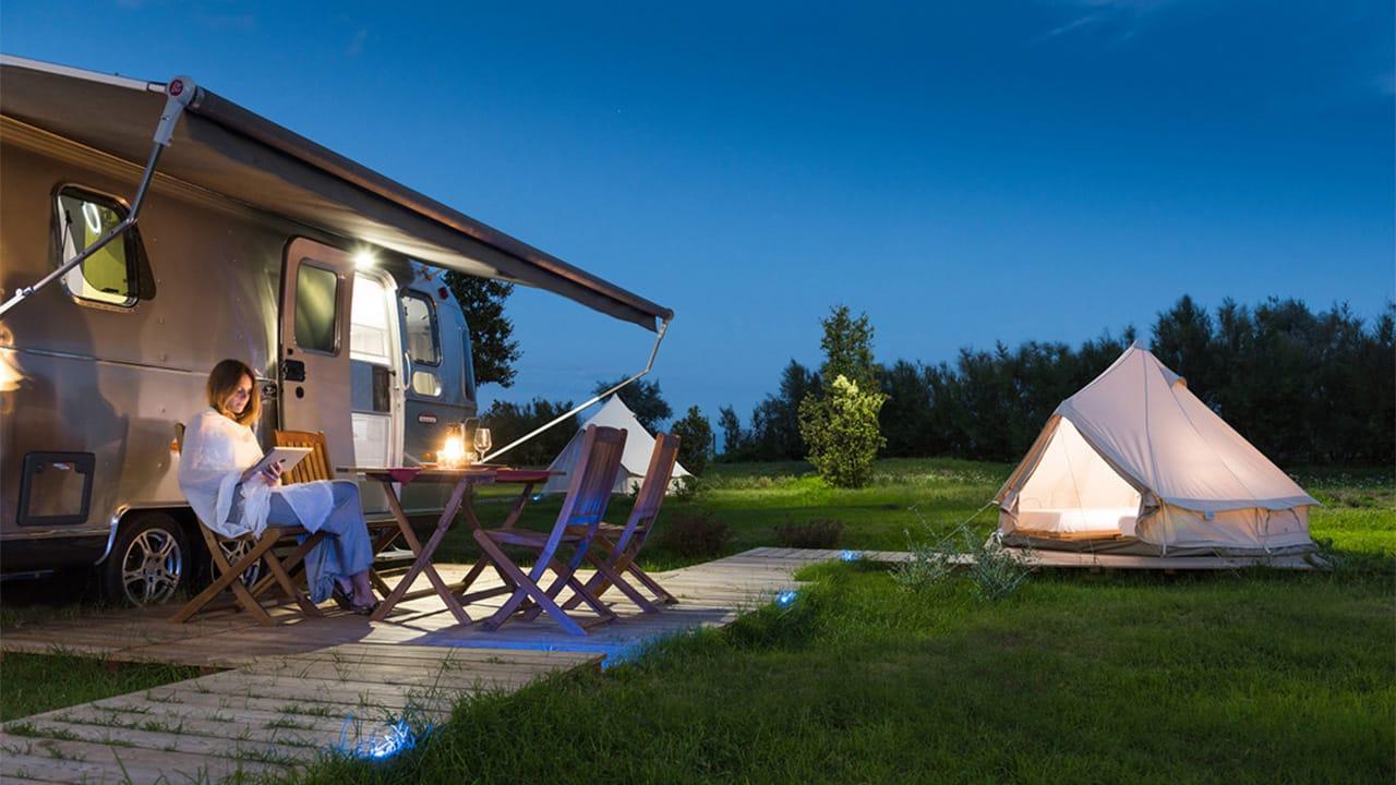 Ein Airstream und ein Zelt am Abend beim Glamping in Italien
