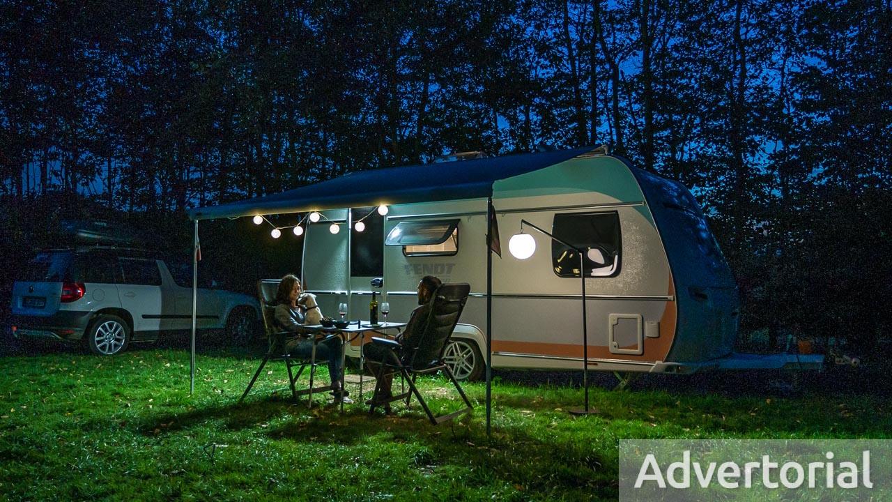 Ein Paar am Abend vor dem Wohnwagen mit tollen outdoor Lampen im Test