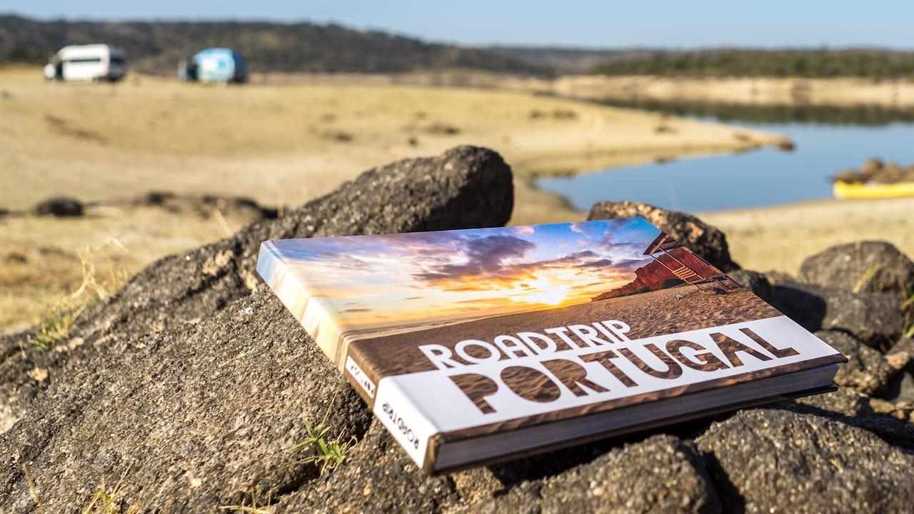 Ein Buch ueber Tipps und Informationen zu einem Roadtrip in Portugal auf einem Stein