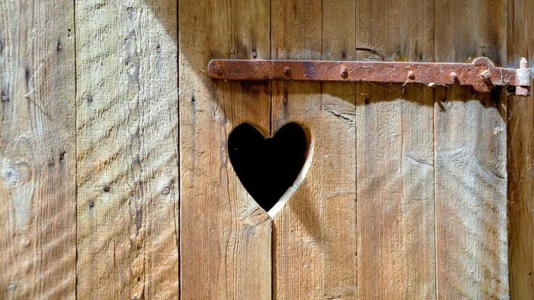 Ein Klohaeuschen aus Holz mit Herz in der Mitte