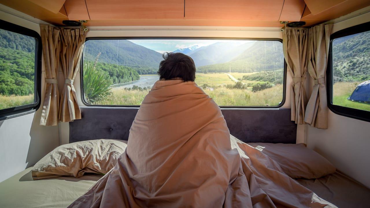 Ein Mann blickt aus dem Fenster mit Bettwaesche und Spannbettlaken im Camper
