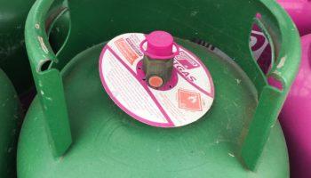 Eine gruene Gasflasche in Portugal mit rosa Ventil