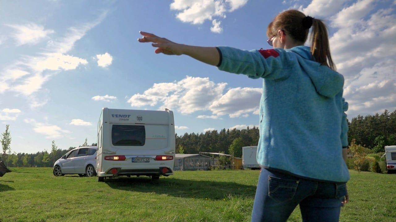Eine Frau beim Einweisen eines Campers