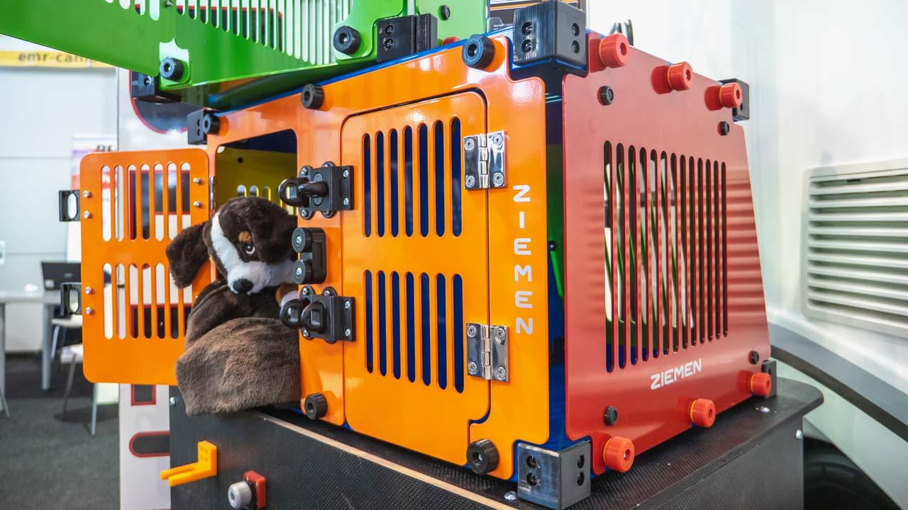 Blick auf eine orange-rote Pet-Save-Box von Ziemen mit einem Plüschhund, der aus der geöffneten Tür schaut und einer grünen Hundebox darauf.