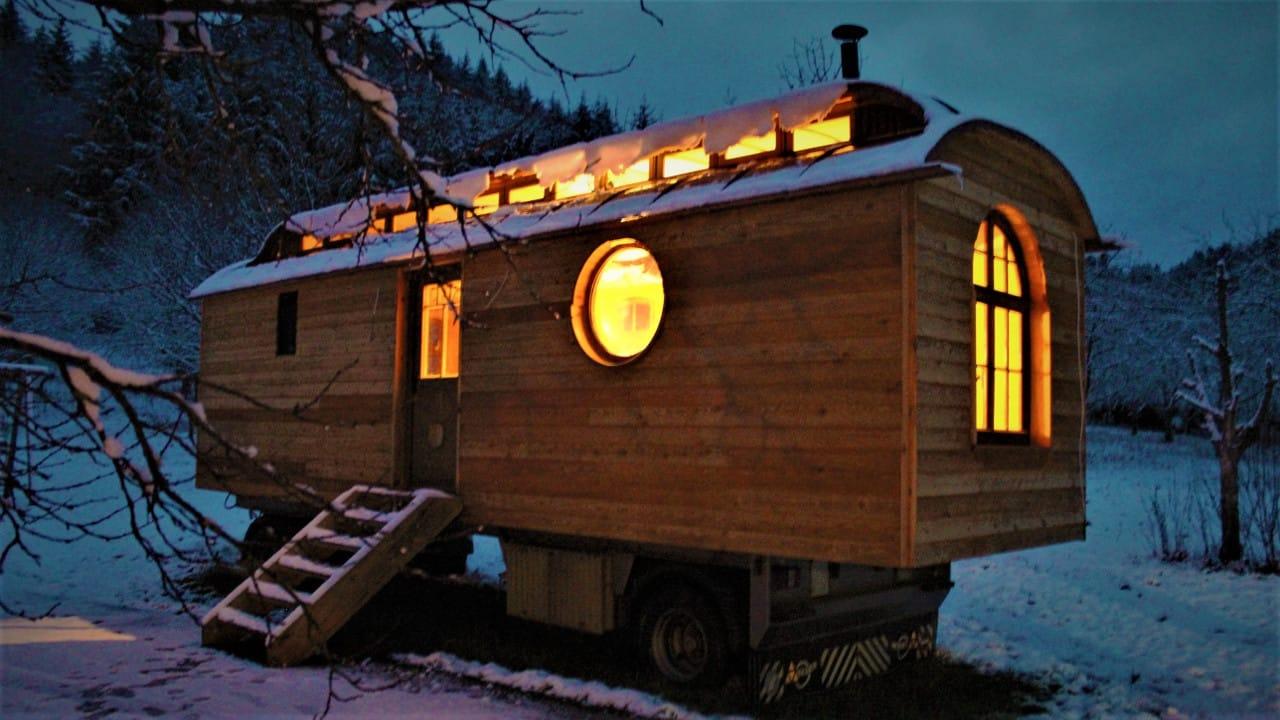 Ein beleuchteter Bauwagen bei Nacht
